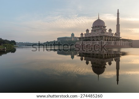 Sunrise at Petrajaya Muslim Mosque in Kuala Lumpur Malaysia. The morning fog has lifted revealing a serene reflection of the mosque on the still water with the early morning light of the sun.