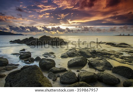 sunrise at rocky beach in terengganu, malaysia. image taken with long exposure,custom white balance. slightly soft due to long exposure