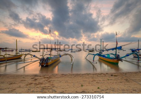 Sunrise at Sanur Beach Bali with traditional balinese jukung boat on foreground - stock photo