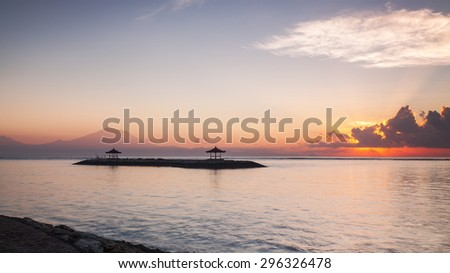 Sunrise at Sanur Beach of bali, Indonesia. Sun rays lite up the thin layers of mist warm up Mount Agung in the background. - stock photo