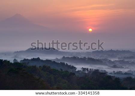 Sunrise at Setumbu hill with the view of Borobudur and Merapi - stock photo