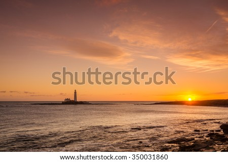 Sunrise at St Mary's Lighthouse / St Mary's Lighthouse on a tiny island just north of Whitley Bay on the coast of North East England. At low tide a causeway allows access - stock photo