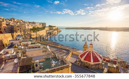 Sunrise at the Grand Harbour of Malta with the ancient walls of Valletta - stock photo