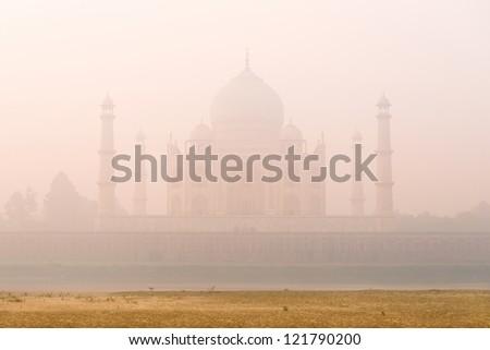 Sunrise at the mystic foggy Taj Mahal, view from Yamuna River, India - stock photo