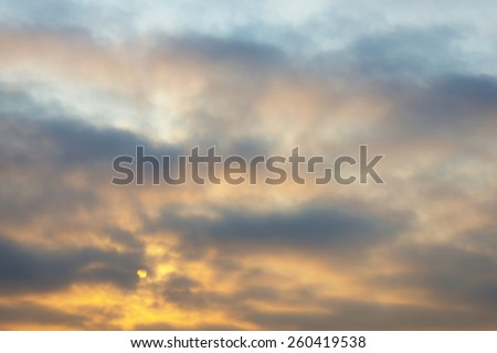 Sunrise behind clouds in winter - stock photo