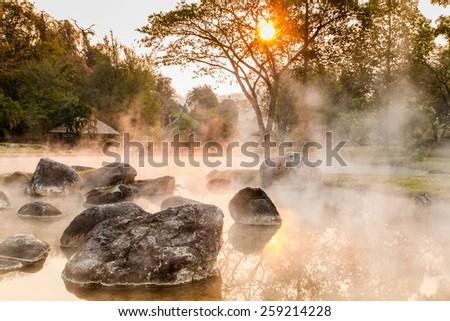 Sunrise behind hot spring - stock photo