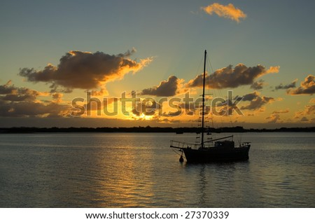 Sunrise breaks over classic old yacht in the still of the morning. - stock photo