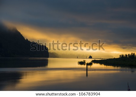 Sunrise clouds reflected in the Columbia River - stock photo