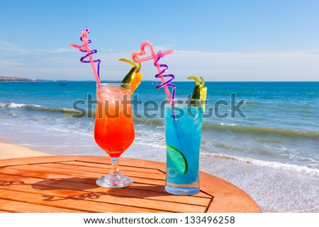Sunrise cocktail and cocktail blue lagoon on the table on the background of blue sea and sky - stock photo