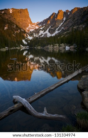 Sunrise, Dream Lake. The warm morning sun lights Hallett Peak and is reflected in the calm waters of Dream Lake in Rocky Mountain National Park. - stock photo