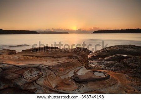 Sunrise from the pretty sandstone swirled rocks at Edwards Beach, Balmoral with views east to the Heads, entrance to Sydney Harbour as sunrays stream from behind clouds welcoming another new day.