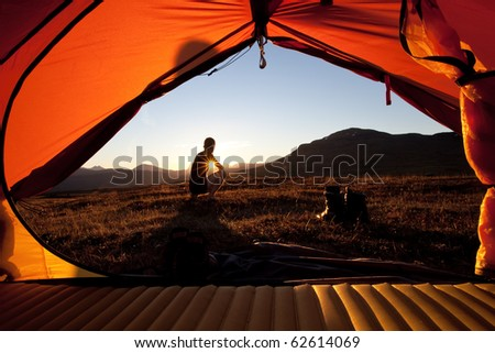 Sunrise, hiker and tent - stock photo