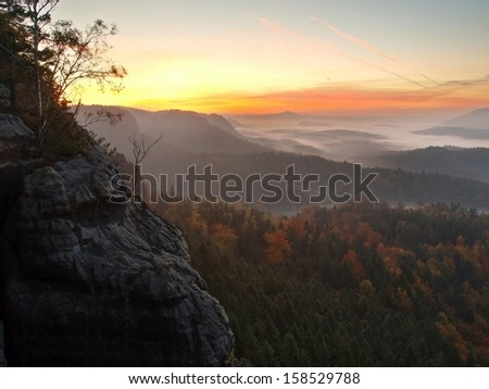 Sunrise in a beautiful mountain of Czech-Saxony Switzerland. Sandstone peaks and hills increased from foggy background, the fog is orange due to sun rays.