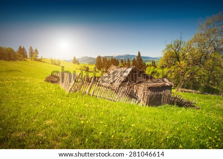 Sunrise in a spring village with broken old wooden house in a valley. - stock photo
