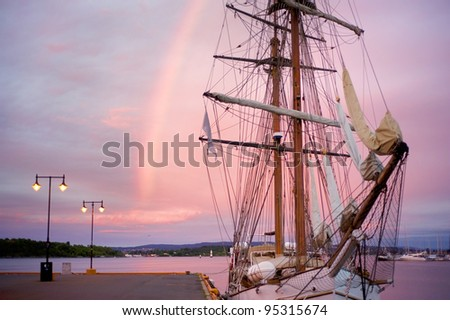 Sunrise in Oslo. White sailing yacht, pier and a rainbow - stock photo