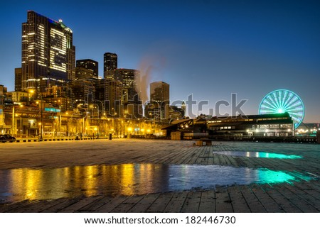 Sunrise in Seattle with reflection of the city on ice on the pier.   12 man support on the building. - stock photo