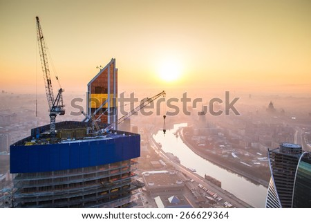 Sunrise in the foggy day over Moscow. Top view from building under construction - stock photo