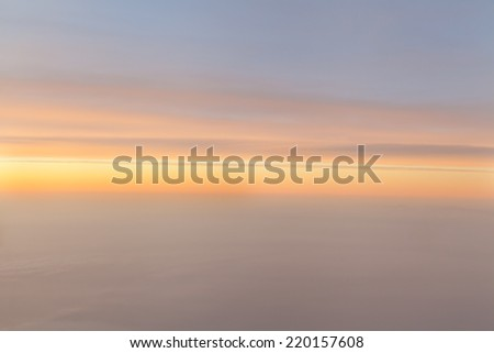 Sunrise in the horizon with foggy cloudscape - stock photo