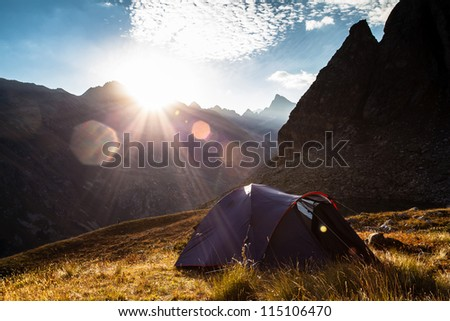 Sunrise in the mountains and the tent - stock photo
