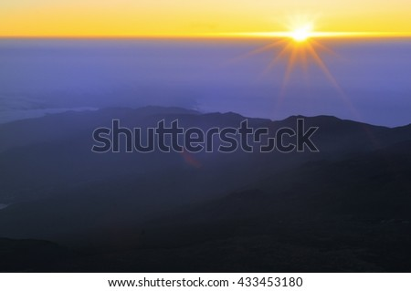 Sunrise in the mountains. View with rising sun and silhouettes of mountains from peak of Teide Tenerife, Canary islands, Spain - stock photo