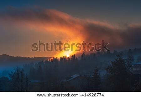 Sunrise landscape. Beautiful morning sun over forest through the dense fog clouds at Carpathian mountains. Ukraine. - stock photo