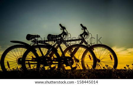 Sunrise landscape with a couple of bike on sunset cloudy sky background . Copy space for inscription  - stock photo