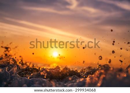 Sunrise light shining on ocean wave with orange tones - stock photo