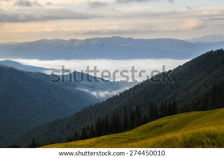 Sunrise mountains landscape with foggy valleys and forests and pink clouds - stock photo