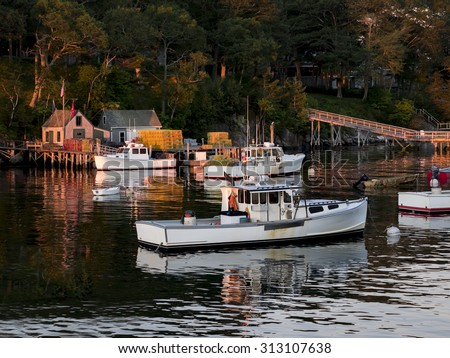 Sunrise on a Maine harbor in late summer with lobster boats moored. - stock photo