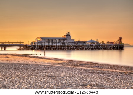 Sunrise on Bournemouth Beach with the Pier in the background. - stock photo