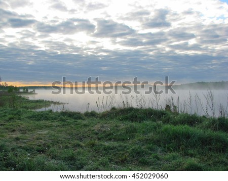 Sunrise on early morning on a river with quite water and strong fog over when sun rays light through cloudy sky. - stock photo