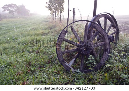 Sunrise on foggy autumnal landscape with two antique horse carriage wooden wheels