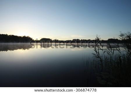 Sunrise on forest lake - stock photo