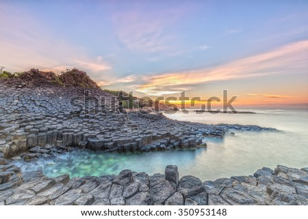 Sunrise on Giant's Causeway with volcanic rocks like hexagonal pillars put them in the sea, far away is the sun rises with the light signal a new day on the sea Beautiful Vietnam - stock photo