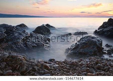 sunrise on rocky sea coast and blurred water