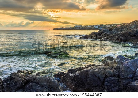 sunrise on the beach, near the small resort village on the edge of the earth. waves breaking on a rocky shore in the sunshine.