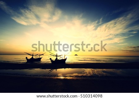 Sunrise on the beach with fishing boats.