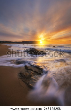 sunrise on the central coast with rocks in the foreground - stock photo