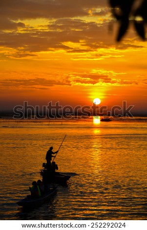Sunrise on the lake with beautiful sky and fisherman boat - stock photo