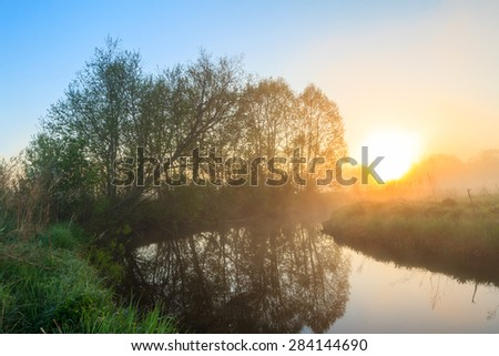 Sunrise on the river with fog. A river whirlpool for the dawn. Trees in fog on the river bank in the morning. The rays of dawn sunlight illuminate the clearing with wildflowers and grass. fine sunrise - stock photo