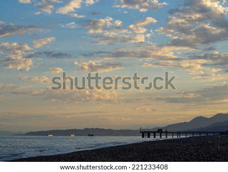 Sunrise on the summer beach with blue hills on the horizon. Panoramic view with a cloudy sky at the coastline. Coastal landscape with a tropical beach, sunset time. - stock photo
