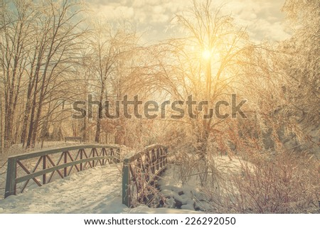Sunrise or sunset glistens through an ice covered treed landscape, after an ice storm during the winter season.  An icy bridge is in the foreground.   Filtered for a retro vintage look.  - stock photo