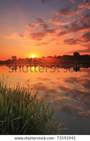 Sunrise over a misty lake on a summer morning