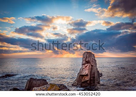 Sunrise over a rocky beach. Colorful clouds reflecting in the sea. - stock photo