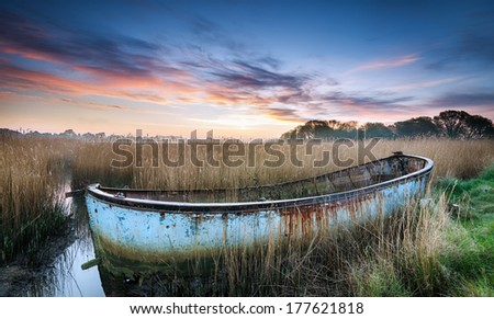 Sunrise over a shipwrecked boat in the backwaters of Poole Harbour in Dorset - stock photo