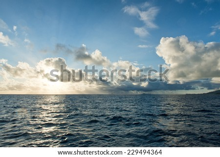 Sunrise over a vast calm ocean with the fiery orb of the sun just rising above the horizon and touching the clouds with a glowing light - stock photo