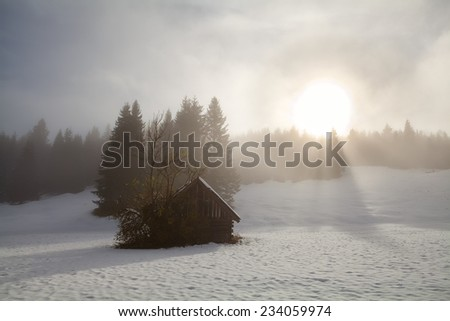 sunrise over alpine snow meadow with old hut, Germany - stock photo