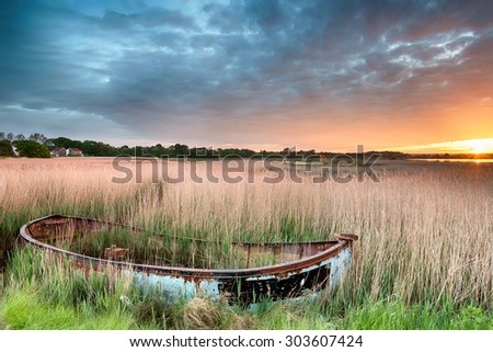 Sunrise over an old fishing boat in reeds at Hamworthy in Poole, Dorset - stock photo