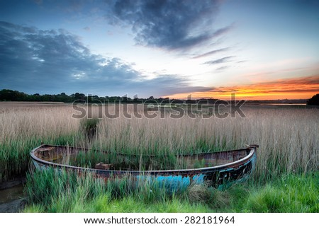Sunrise over an old fishing boat washed up in reeds at Poole Harbour on the Dorset coast - stock photo