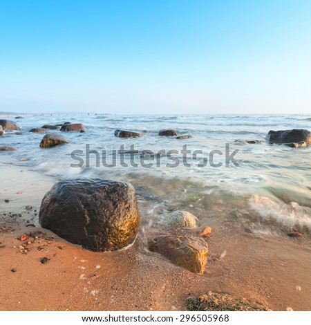 Sunrise over Baltic Sea on island Rugen, Germany. This is tilt-shift frame, focus is on the stones through the entire frame. Long exposure to show movement of water. Space for your text